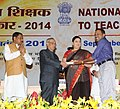 Pranab Mukherjee presenting the National Award for Teachers-2014 to Shri Niyas Chola, Kerala, on the occasion of the 'Teachers Day', in New Delhi. The Union Minister for Human Resource Development, Smt. Smriti Irani.jpg