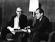 Präsident Nixon und NASA-Administrator James Fletcher sitzen mit einem Modell des Space Shuttles