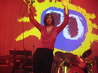 Primal Scream performing live with the cover of their album Screamadelica in the back Primal Scream performing Screamadelica live in Paradiso, Amsterdam Screamadelica's iconic cover image (6127942325).jpg