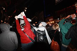 On the crowded sidewalk of a street at night, a person in a red jacket attempts to hold up a sign, and a woman in a black jacket and wearing a gray scarf and hat reaches up to grab the sign.