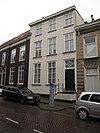 foto van Huis met gebosseerd gepleisterde lijstgevel en trap met bordes voor de ingang