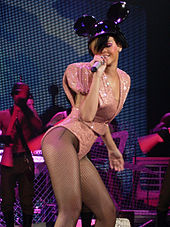 A woman wearing a high waisted pink sparkly outfit with large shoulder pads performing on a stage