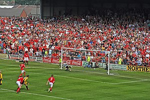 An action scene from a soccer match, played on a sun-soaked summer's day. Before an old-fashioned terraced stand packed to the rafters with fans, mostly clad in red, a penalty kick has just been taken by a player wearing a red shirt and white shorts. The ball is nestled in the bottom-right-hand corner of the net, with the goalkeeper helpless on the opposite side of his goal. Behind the penalty taker, a few players from each team can be seen on the edge of the penalty area.