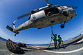 Sailors attach cargo to a helicopter. (10876052654).jpg
