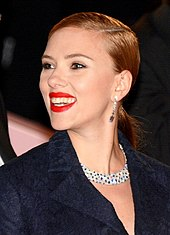 Scarlett Johansson, wearing a dark blue coat, smiles to her left.