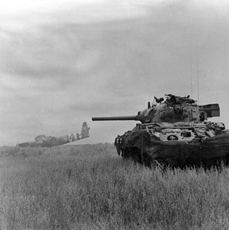 M4 Sherman - A Sherman DD amphibious tank of 13th/18th Royal Hussars in action against German troops using crashed Horsa gliders as cover near Ranville, Normandy, 10 June 1944