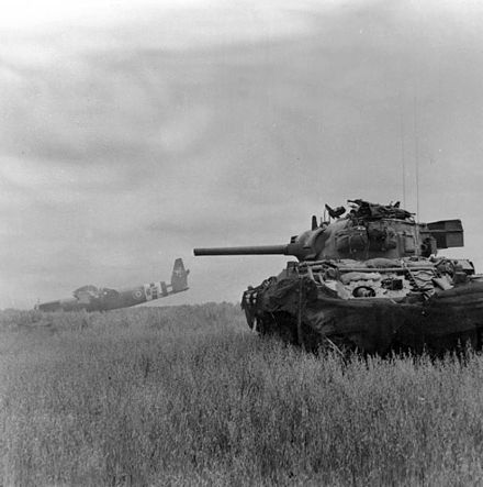 A Sherman DD amphibious tank of 13th/18th Royal Hussars in action against German troops using crashed Horsa gliders as cover near Ranville, Normandy, 10 June 1944 Sherman tank and Horsa glider.jpg