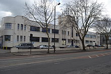 Long white building in winter, with trees in front