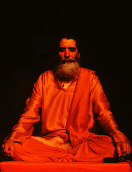 A colour photo dated 1995 of Swami Janakananda clad in orange-coloured clothes, pictured sitting with eyes closed in the yoga pose ardha padmasana (half lotus pose), his wrists are resting on his knees, and his fingers are forming a variation of the yoga gesture chin mudra. He is equipped with a lapel microphone which together with his body posture suggests that he is instructing a meditation.