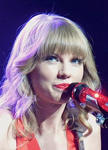 Taylor Swift, with curled hair and red painted lips, smiles slightly  at the crowd