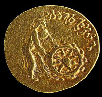 Tillya Tepe - The Tillya Tepe Buddhist coin, with naked deity wearing chlamys cape and petasus hat pushing the Wheel of the Law. Kabul Museum.