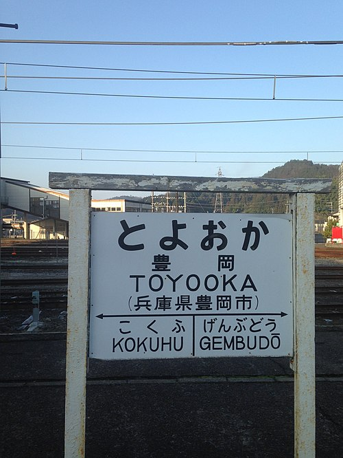 "Former Japan National Railways-style board of Toyooka Station. Between the two adjacent stations, ""GEMBUDO"" follows the Hepburn romanization system, but ""KOKUHU"" follows the Nihon-shiki/Kunrei-shiki romanization system. Toyooka Station Sign.jpg"