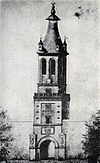 Drawing of a tall tower with a clock and a tapering pyramidal roof; a status is located on top of the pointed roof