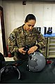 U.S. Air Force Tech. Sgt. Lissy Mayer, a 74th Expeditionary Fighter Squadron noncommissioned officer in charge of aircrew flight equipment, makes adjustments to night vision goggles on a pilot's helmet at Bagram 130429-F-ZX232-039.jpg