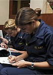 U.S. Navy Midshipman 3rd Class Kendra Mikatarian, front, and Midshipman 2nd Class Ashley Brady fill out liberty mission planning forms in preparation for a port call on the aircraft carrier USS Nimitz (CVN 68) 130808-N-KE148-059.jpg