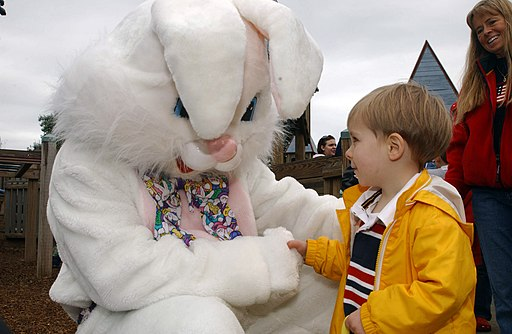 US Navy 070331-N-2143T-002 Chief Culinary Specialist James Willis plays the Easter bunny as he is greeted by children during an Easter egg hunt event