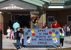US Navy 070401-N-1082Z-001 Lois Davis, training and curriculum supervisor for Naval Air Station (NAS) Oceana Child Development Center (CDC), leads a parade along with education technicians Julia Yarbrough and Alice Fernandez