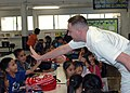 US Navy 071031-N-7138C-047 Senior Chief Religious Program Specialist Peter Dyksterhouse, Pacific Fleet Personal Excellence Partnership coordinator, gives a high-five to a Kalihi Elementary School.jpg
