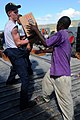 US Navy 080922-N-7955L-112 Aviation Ordnanceman Airmen Travis Pillow, assigned to the amphibious assault ship USS Kearsarge (LHD 3), gives a box of cooking oil to a Haitian citizen during a humanitarian assistance mission to ai.jpg