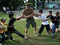 US Navy 091029-N-0120R-442 A Navy Special Warfare Sailor assigned to Joint Special Operations Task Force-Philippines plays a modified version of tug-of-war with local children at the first children's day event.jpg