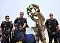 US Navy 100717-N-6214F-015 Members of the U.S. Navy parachute demonstration team, the Leap Frogs, deliver a wreath to an awaiting SEAL for the opening ceremony of the capabilities exercise.jpg