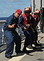 US Navy 110422-N-NL541-103 Culinary Specialist 1st Class Lucio Diaz, a member of the damage control training team, shows Sailors how to handle a fi.jpg