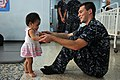 US Navy 111025-N-WW409-058 Lt. j.g. Tim Cox, assigned to the guided-missile destroyer USS Mustin (DDG 89), plays with a child at the Pattaya Orphan.jpg