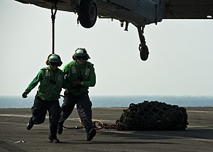 US Navy 111229-N-BT887-517 Logistics Specialist Seamen Tyler Thiebault and Tomiya Norris clear the area after attaching a hook to an MH-60S Sea Haw.jpg
