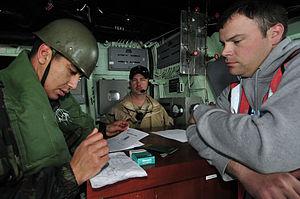 US Navy 120202-N-IZ292-079 Royal Moroccan Navy 1st Sgt. Hamid Karada checks the identification papers of Chief Gunner's Mate Sean Holmes, simulatin.jpg