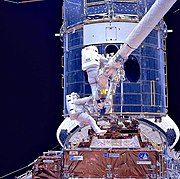 Astronauts installing corrective optics during SM1