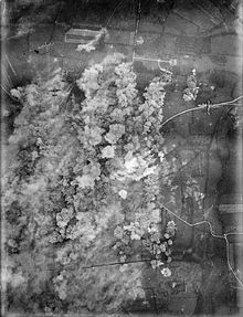 A photo taken from the air, plumes of smoke rise over a town.