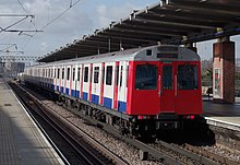 A photograph of a D Stock train departing West Ham on a westbound service.