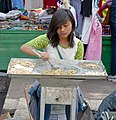 Young woman stirring food at Mexico City street market.jpg