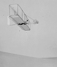 Wilbur Wright pilots the 1902 glider over the Kill Devil Hills, 10 October 1902. The single rear rudder is steerable; it replaced the original fixed double rudder. photo taken by Lorin Wright.
