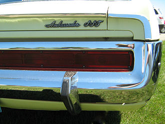 Bumper (car) - Rear bumper with integrated tail lamps and a rubber-faced guard