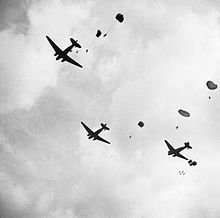 Three aircraft with parachutists leaving from the doors