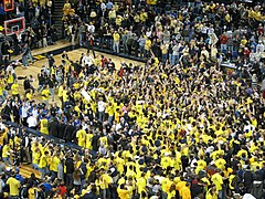 Fans wearing maize swarm the basketball court in celebration.