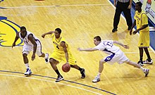 A basketball player in a maize colored uniform dribbles between defenders in white uniforms.