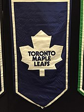 A banner featuring an old Maple Leaf logo, featuring an eleven pointed white maple leaf on a blue background.