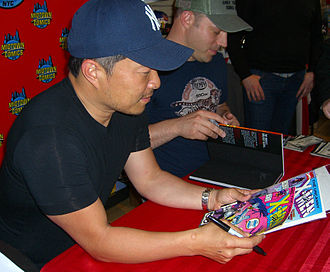 Uncanny X-Men - Jim Lee holding some of the 1990s issues of the series on which he rose to stardom as an artist