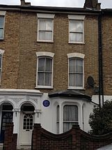 ekstero de blanka domo, kun blua plako sur antaŭa muro