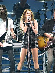 A female teen in a black leather hotpants suit sings into a microphone on a blue-hued stage. Behind her, two electric guitarists and a drummer play their instruments.