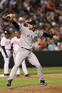 "A man in a grey baseball uniform with ""New York"" on the chest wearing a baseball glove and a dark cap winds up to throw with his left hand."