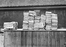 Black and white photograph of two stacks of documents on a table. The stack on the right is much larger than that on the left.