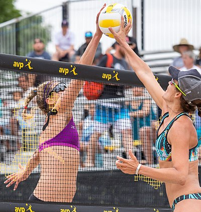 "Two opposing players simultaneously contact the ball above the net with open hands, known as a ""joust"". The receiving team is entitled to another three contacts. AVP Professional Beach Volleyball in Austin, Texas (2017-05-21) (35525941495).jpg"