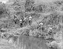 Soldiers slowly advance up a hill along the side of a waterway
