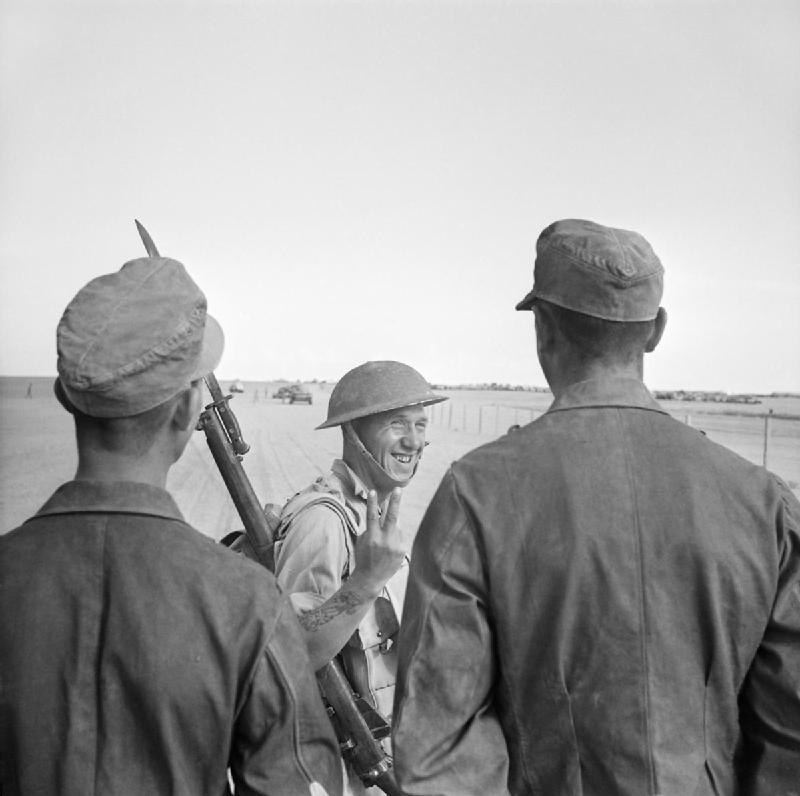 A British soldier gives a V-for-Victory sign to German prisoners captured at El Alamein, 26 October 1942. E18522