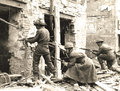 A Canadian soldier fires on the enemy in a house in Caen, July 10, 1944..png