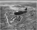 A Marine observation plane flies low over Naha, capital of Okinawa. On this flight, the tiny ship drew small arms and... - NARA - 532379.tif