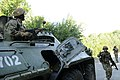 A Ukrainian Soldier gives commands to a soldier providing security from a BTR-80.jpg
